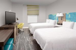 A bed or beds in a room at Hampton Inn Miami Airport East