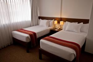 A bed or beds in a room at Tierra Viva Puno Plaza
