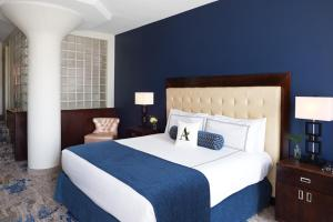 A bed or beds in a room at Atheneum Suite Hotel