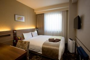 A bed or beds in a room at Shinsaibashi Grand Hotel Osaka