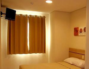 Uma TV ou centro de entretenimento em Hotel Eden