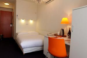 A bed or beds in a room at Multatuli Hotel