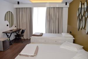A bed or beds in a room at Adonis City Hotel