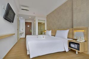 A bed or beds in a room at Whiz Prime Hotel Basuki Rahmat Malang