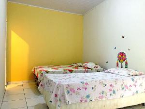 A bed or beds in a room at Pousada CPA