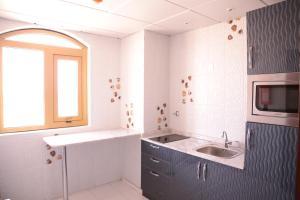 A kitchen or kitchenette at Al Sadarah Apartment Hotel