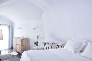 A bed or beds in a room at Katikies Kirini Santorini - The Leading Hotels Of The World