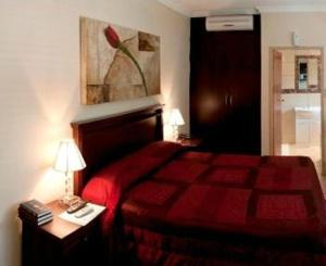A bed or beds in a room at Rustenburg Boutique Hotel