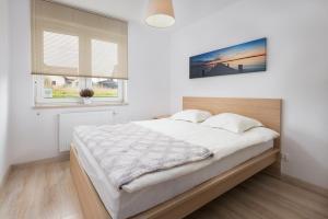 Łóżko lub łóżka w pokoju w obiekcie Rybacka Apartament