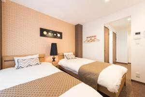 A bed or beds in a room at Komachi Hotel Nipponbashi