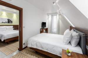A bed or beds in a room at Hampton By Hilton Gdansk Oliwa