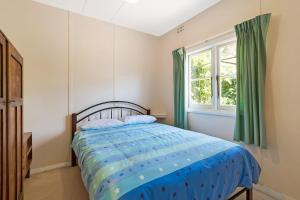 A bed or beds in a room at Pet Friendly Beach Cottage @ Ballingalla