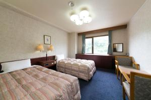 A bed or beds in a room at Road Inn Toba