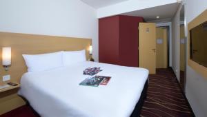 سرير أو أسرّة في غرفة في ibis Seef Manama