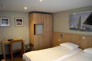 A bed or beds in a room at Hotel Honfleur