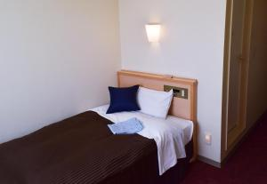 A bed or beds in a room at Hotel All In Stay Hakodate