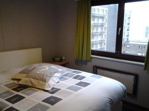 Een bed of bedden in een kamer bij Zonnig Appartement met Zeezicht