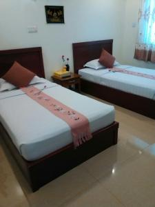 A bed or beds in a room at Kyaik Hto Hotel - The Golden Rock Pagoda