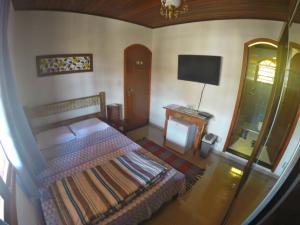 Cama ou camas em um quarto em Suítes do Alex