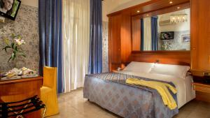 A bed or beds in a room at Hotel Assisi