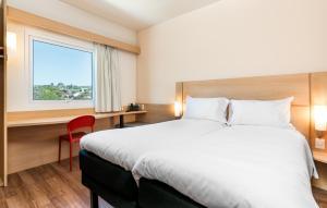 Cama o camas de una habitación en ibis Puerto Montt
