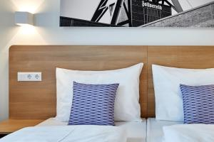 A bed or beds in a room at McDreams Hotel Essen