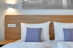 A bed or beds in a room at McDreams Hotel Düsseldorf-City