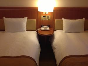 A bed or beds in a room at Star Hotel Yokohama