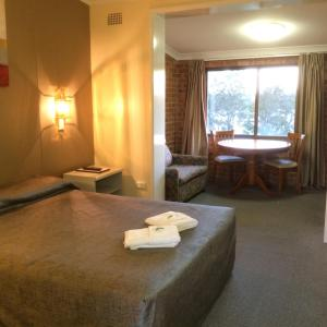 A bed or beds in a room at Riverview Motor Inn