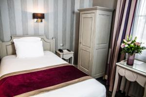 A bed or beds in a room at Hôtel Concordia Le Mans Centre Gare