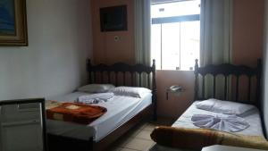 A bed or beds in a room at Adry Hotel Inn Itajaí Navegantes