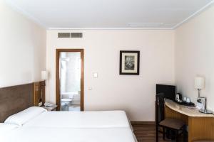 Säng eller sängar i ett rum på Hotel Inglaterra
