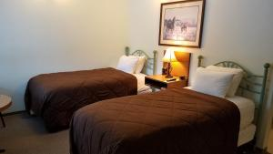 A bed or beds in a room at White Willow Motel