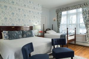 A bed or beds in a room at Four Chimneys Inn