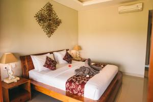 A bed or beds in a room at The Runik Ubud