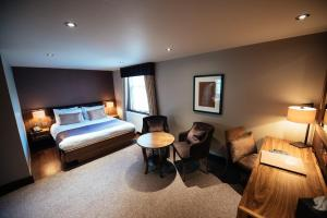 A bed or beds in a room at Busby Hotel