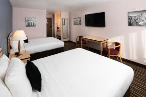 A bed or beds in a room at SYLO Hotel Denver Airport, a Ramada by Wyndham