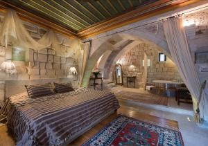 A bed or beds in a room at Anatolian Houses Cave Hotel