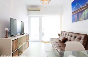 Uma TV ou centro de entretenimento em Simple Chic Belem Apartment