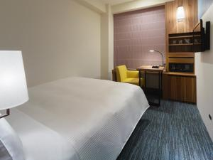 A bed or beds in a room at Mitsui Garden Hotel Kumamoto