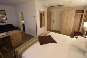 A bed or beds in a room at Hotel zum Adler - Superior