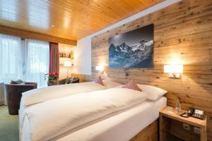 Кровать или кровати в номере Hotel Bernerhof Grindelwald