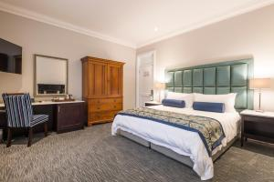 A bed or beds in a room at Avondale Boutique Hotel