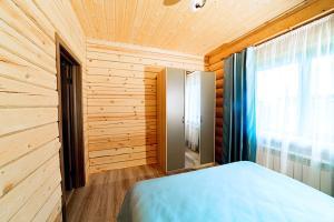 """Кровать или кровати в номере Гостевые дома """"Охотничьи традиции"""""""