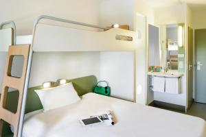 A bed or beds in a room at ibis budget Augsburg City