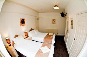 A bed or beds in a room at Stanley View Guest House & Hotel