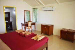 A bed or beds in a room at Palolem Beach Resort