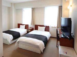 A bed or beds in a room at APA Hotel Akita-Senshukoen