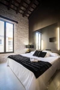 A bed or beds in a room at Cosy Rooms Embajador