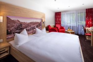A bed or beds in a room at Alm- & Wellnesshotel Alpenhof